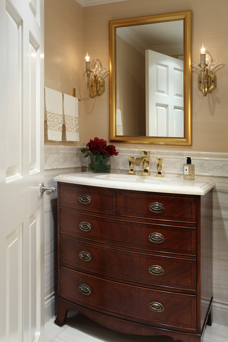 Powder room custom wood cabinetry with gold rectangular mirror and faucet. Two crystal sconces on each side of mirror.
