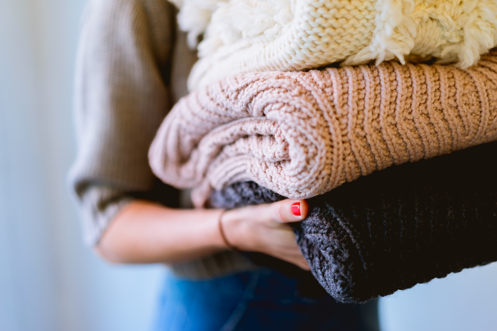 Woman carrying folded sweaters